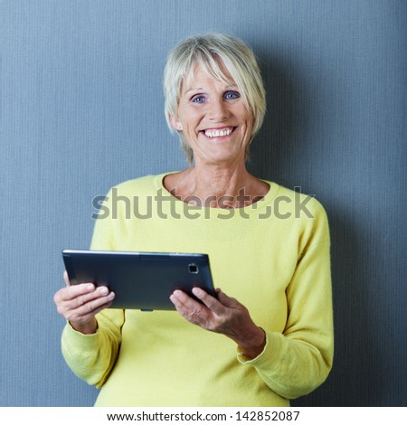 Portrait of a senior woman working on a tablet and smiling. - stock photo