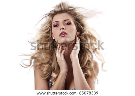 portrait of a sensual girl with her hair flying in the wind posing on white - stock photo