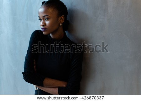Portrait of a serious african or black american woman with arms folded standing over gray background and looking away - stock photo