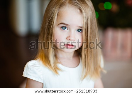 Portrait of a serious baby girls blonde with straight hair, close up - stock photo