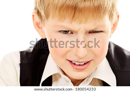Portrait of a serious boy stares intently into the camera. Isolated over white. - stock photo
