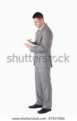 Portrait of a serious businessman taking notes against a white background - stock photo