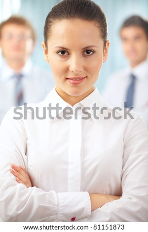 Portrait of a serious businesswoman standing with her hands crossed - stock photo