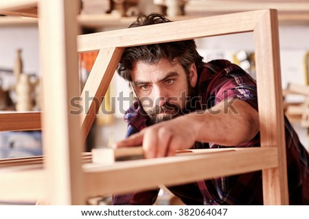 Portrait of a serious craftsman looking focused and serious as he is sanding down a wooden piece that he has manufactured in his woodkwork studio - stock photo