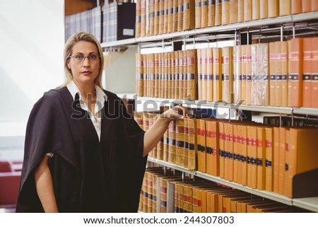 Portrait of a serious lawyer with reading glasses in library - stock photo