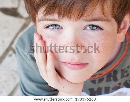 Portrait of a serious looking child - stock photo