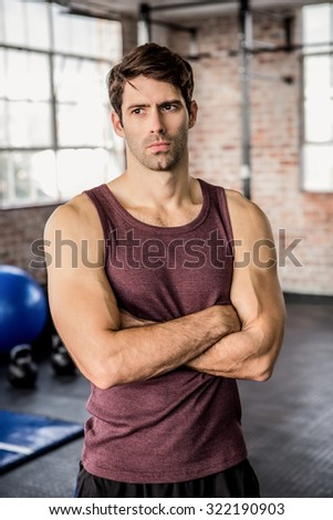 Portrait of a serious man with arms crossed at the gym - stock photo