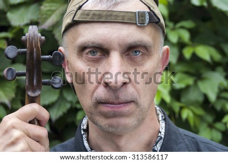 Portrait of a serious matured man, musician, posing with violin, garden in the blurred background - stock photo