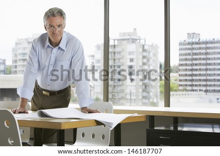 Portrait of a serious middle aged businessman leaning on desk in office - stock photo