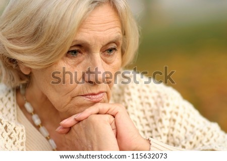 Portrait of a serious middle-aged women a soft autumn background - stock photo