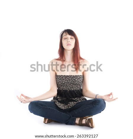 Portrait of a Serious Pretty Young Woman in Trendy Outfit Sitting in a Yoga Pose with Eyes Closed, Isolated on White Background. - stock photo