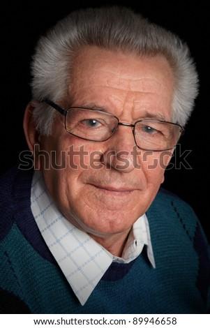 Portrait of a serious senior man on black background - stock photo