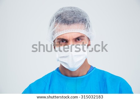 Portrait of a serious surgeon looking at camera isolated on a white background - stock photo
