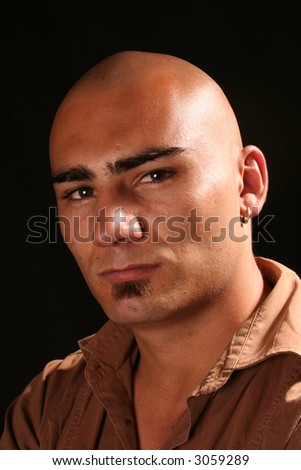 Portrait of a serious young shaved head eyes open - stock photo