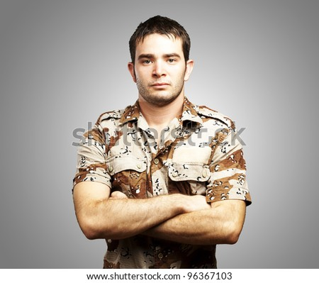 portrait of a serious young soldier standing against a grey background - stock photo