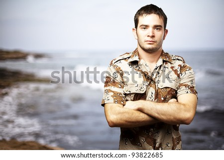 portrait of a serious young soldier standing against a sea background - stock photo