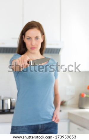 Portrait of a serious young woman holding out knife in the kitchen at home - stock photo