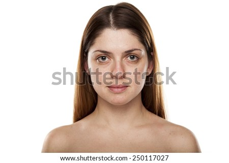 Portrait of a serious young woman with no make up standing on a white background in studio. - stock photo
