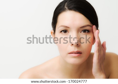 Portrait of a sexy brunette Caucasian young woman looking in the mirror, observing facial wrinkles, first sign of aging - stock photo