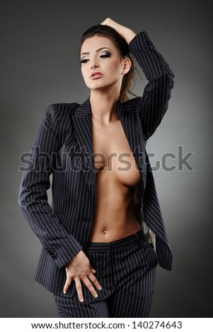 Portrait of a sexy businesswoman posing on gray background - stock photo