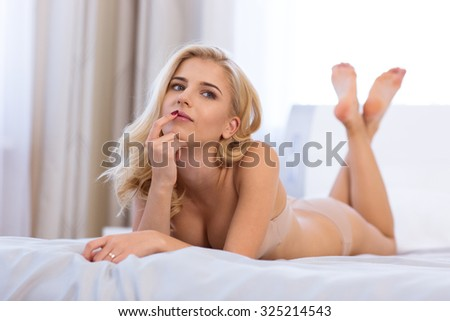 Portrait of a sexy cute woman in lingerie lying in the bed  - stock photo