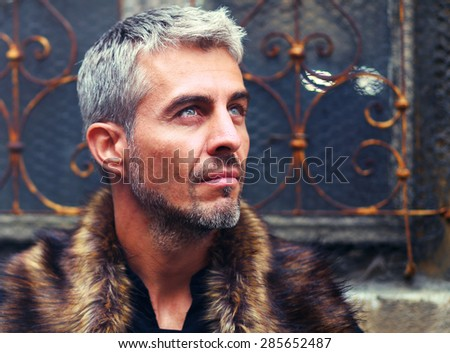 Portrait of a sexy man in wolf  fur and ornamental medieval window on background. - stock photo