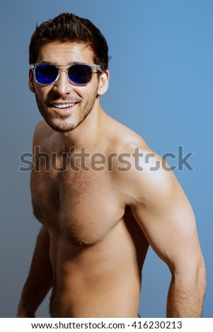 Portrait of a sexy muscular young man in sunglasses. Studio shot. - stock photo