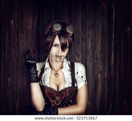 Portrait of a sexy steampunk woman with big breast wearing vintage corset and retro goggles on old wooden background - stock photo