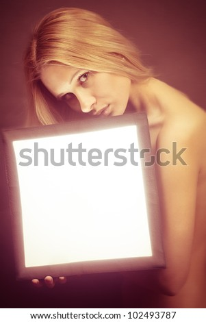 portrait of a sexy young female fashion model holds light box with copyspace - stock photo