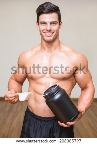 Portrait of a shirtless body builder holding a scoop of protein mix in gym - stock photo
