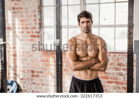 Portrait of a shirtless man with arms crossed at the gym - stock photo