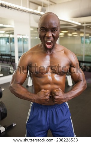 Portrait of a shirtless muscular man shouting while flexing muscles in gym - stock photo