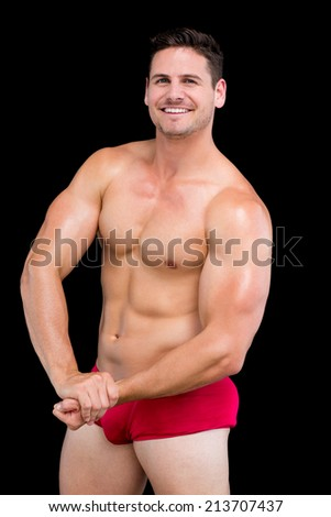 Portrait of a shirtless muscular man standing over black background - stock photo