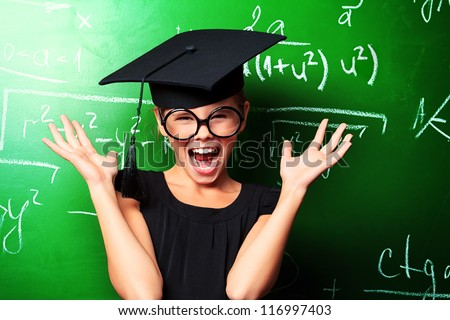 Portrait of a shocked schoolgirl in academic hat at a classroom. - stock photo