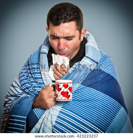 Portrait of a sick man with the flu coughing and holding a warm tea cup - stock photo