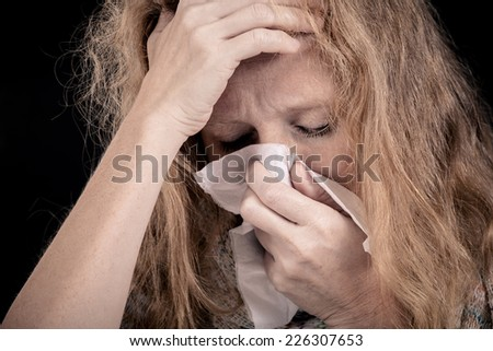Portrait of a sick woman covering the face with a napkin - stock photo