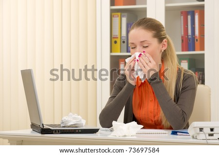 Portrait of a sick young business woman blowing her nose on her workplace - stock photo