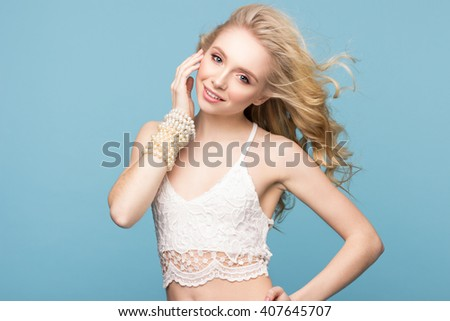 Portrait of a slender young woman with long wavy blond hair. Perfect fresh skin. Isolated on light blue background. Youth, skin care concept. Looking at camera. Beautiful smile. - stock photo