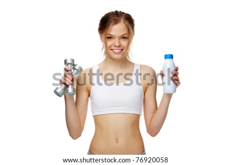 Portrait of a slim girl holding a bottle of milk and dumbbells, looking at camera and smiling - stock photo