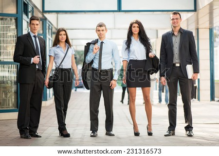 Portrait of a small group of young business people standing in the passage of the building. - stock photo