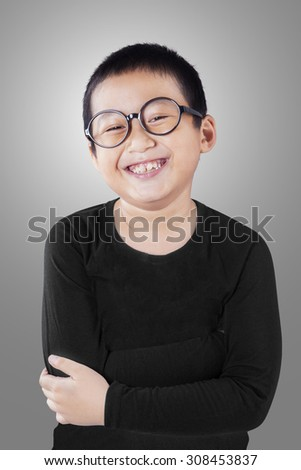Portrait of a smart little boy wearing glasses in the studio and smiling at the camera - stock photo