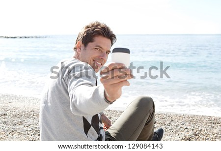 "Portrait of a smart man sitting on a pebble beach, turning around to take a picture with his ""smart phone"", smiling. - stock photo"