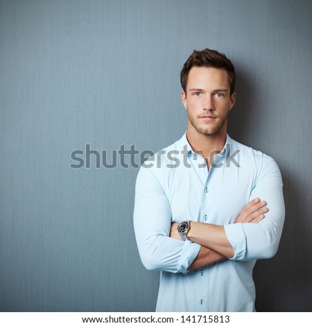 Portrait of a smart serious young man standing against blue background - stock photo