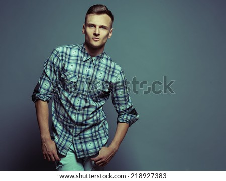 Portrait of a smart serious young man standing against blue background in jeans and shirt. Copy space. Close up. - stock photo