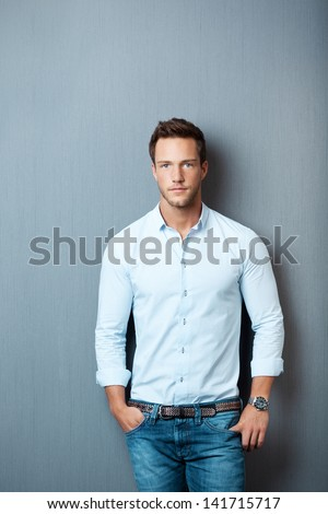 Portrait of a smart young man standing against gray background - stock photo