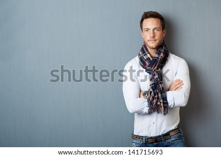 Portrait of a smart young man wearing a scarf standing with arms crossed against blue background - stock photo