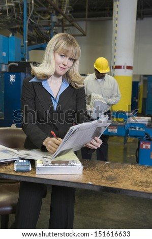 Portrait of a smartly dressed woman with worker in background at newspaper factory - stock photo