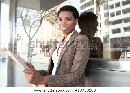 Portrait of a smiling african american business woman looking at camera, with financial newspaper stock market by reflective glass office, outdoors. Professional black woman in finance city exterior. - stock photo
