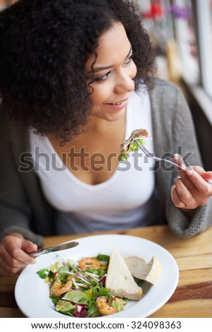Portrait of a smiling african american woman eating in restaurant - stock photo