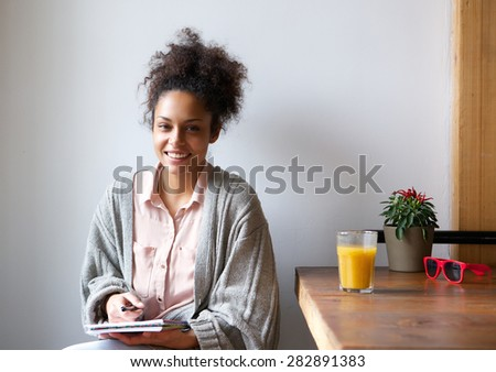 Portrait of a smiling african american woman sitting at home with pen and paper - stock photo